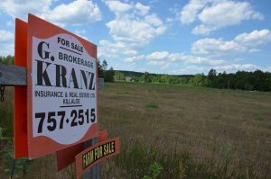 A for sale sign in a beautiful field